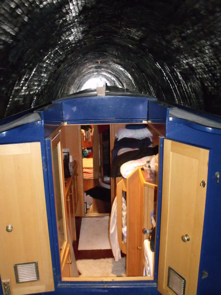 Lights on, doors and windows open to help us see in the dark tunnel as we drive our narrowboat through